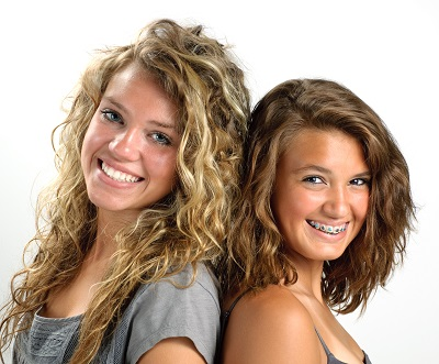 Two teenage girls in Sherman Oaks, CA smiling with braces at Dougherty Orthodontics